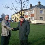 Far away shot of Grahame Morris shaking hands at tree planting
